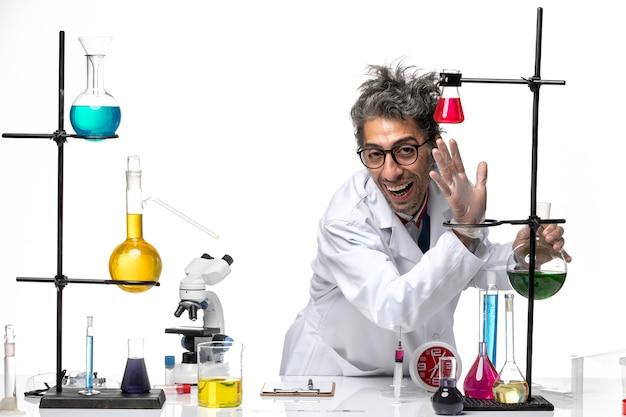 Scienziato maschio di vista frontale in vestito medico che lavora con diverse soluzioni