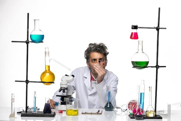 Scienziato maschio di vista frontale in vestito medico che lavora con l'iniezione