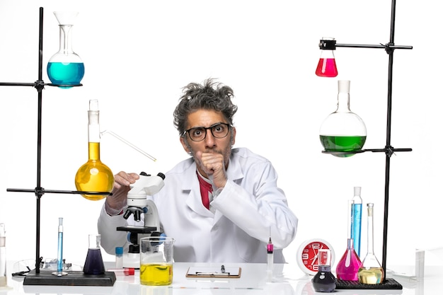 Scienziato maschio di vista frontale in vestito medico che lavora con il microscopio
