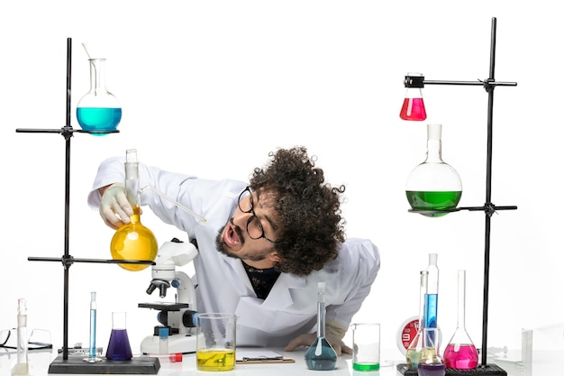 Front view male scientist in medical suit working with solutions on a white space