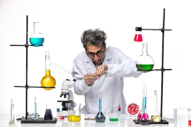 Scienziato maschio di vista frontale in vestito medico che lavora con le soluzioni