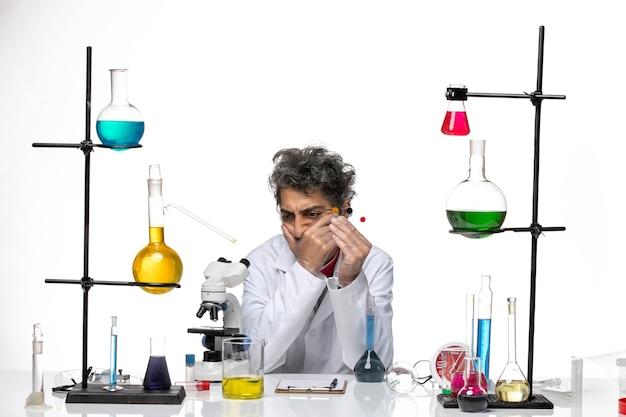 Вид спереди ученый-мужчина сидит перед столом с решениями, думая