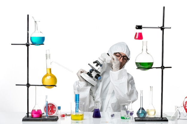 Front view male scientist in special protective suit holding microscope