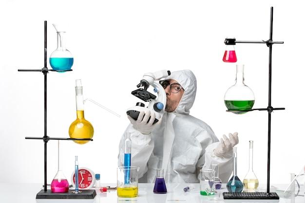 Scienziato maschio di vista frontale nel microscopio della tenuta della tuta protettiva speciale