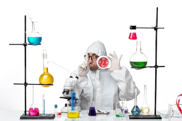 Front view male scientist in special protective suit holding red clocks