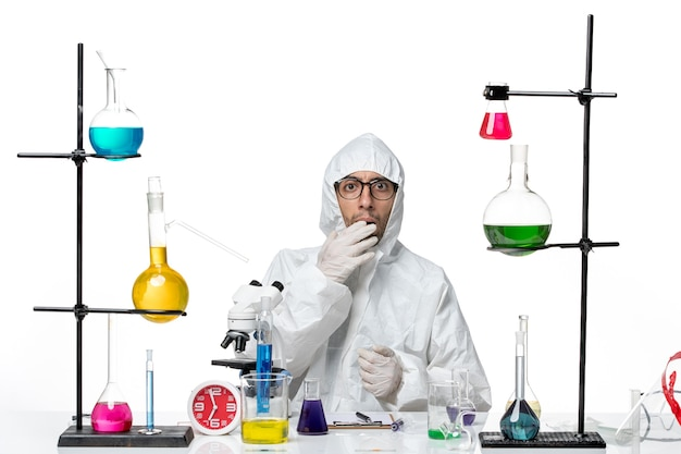 Front view male scientist in special protective suit sitting around desk with solutions