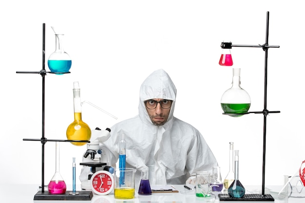Front view male scientist in special protective suit sitting around table with solutions