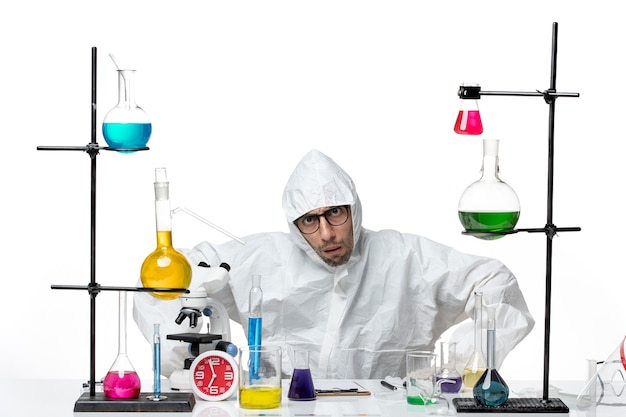 Front view male scientist in special protective suit sitting with different solutions
