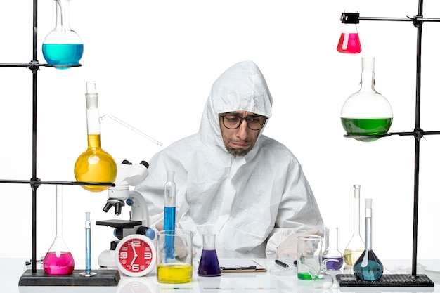 Front view male scientist in special protective suit sitting with solutions feeling sad