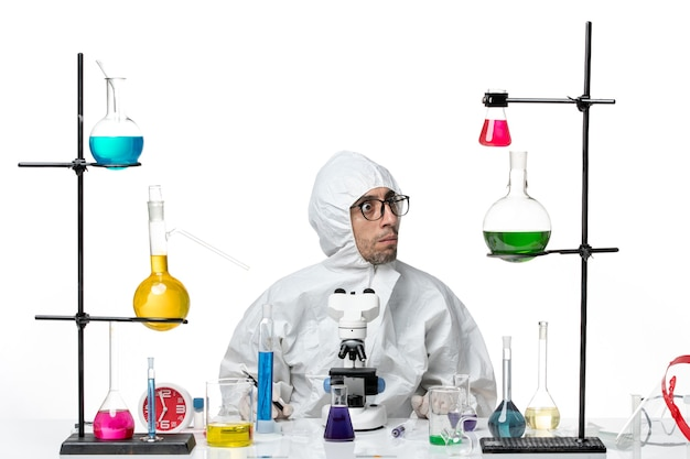 Front view male scientist in special protective suit sitting with solutions holding pen