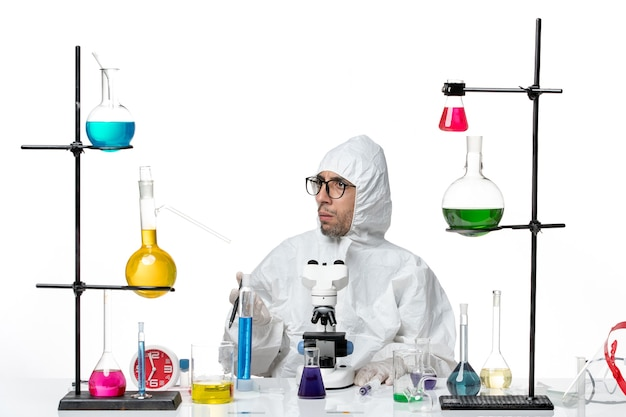 Front view male scientist in special protective suit sitting with solutions