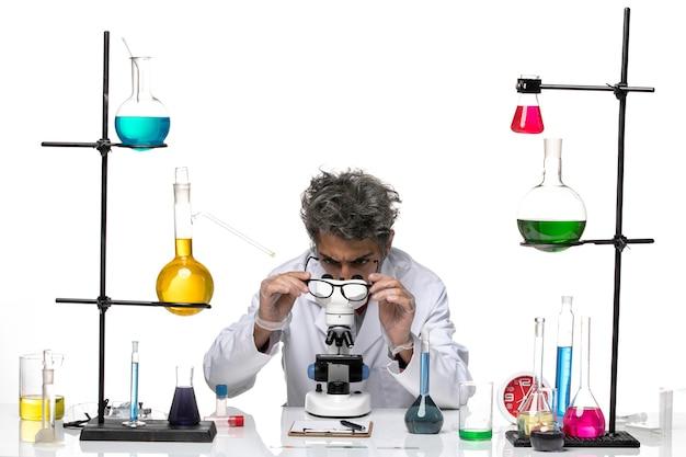 Scienziato maschio di vista frontale in vestito medico bianco che controlla gli occhiali da sole