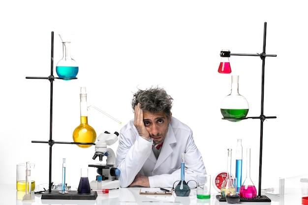 Scienziato maschio di vista frontale in vestito medico bianco che si sente così esausto