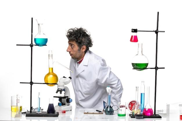 Scienziato maschio vista frontale in tuta medica bianca davanti al tavolo con soluzioni