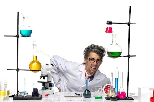 Scienziato maschio vista frontale in tuta medica bianca in piedi da terra