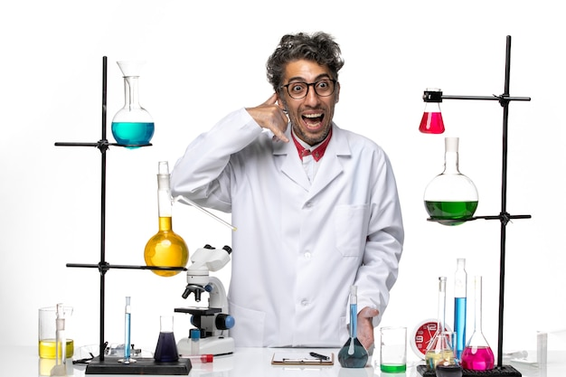 Scienziato maschio di vista frontale in vestito medico bianco in piedi e in posa