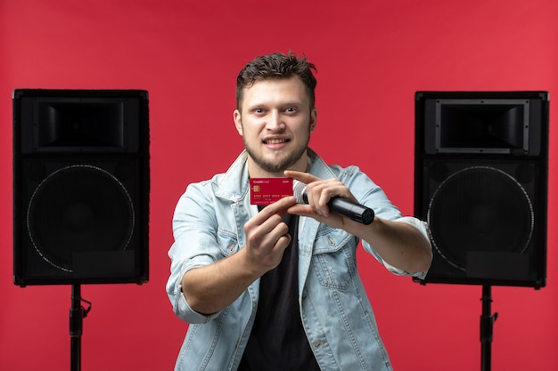 Front view of male singer performing on stage holding bank card on a red wall