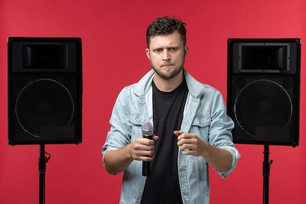 Vista frontale del cantante maschio che si esibisce sul palco con impianto stereo sulla parete rossa