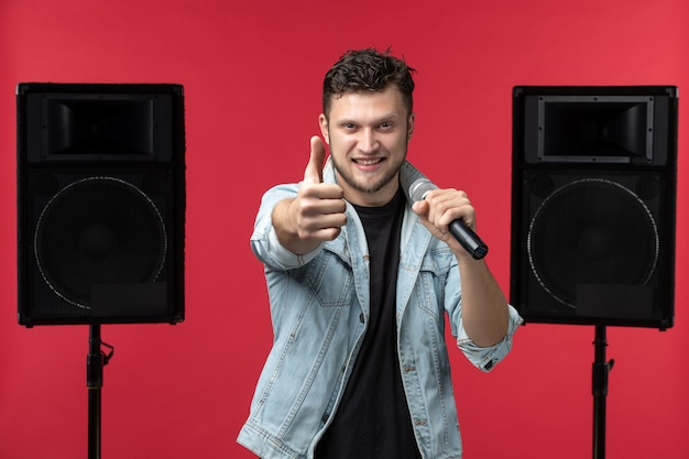 Front view of male singer performing on stage with stereo system on the red wall
