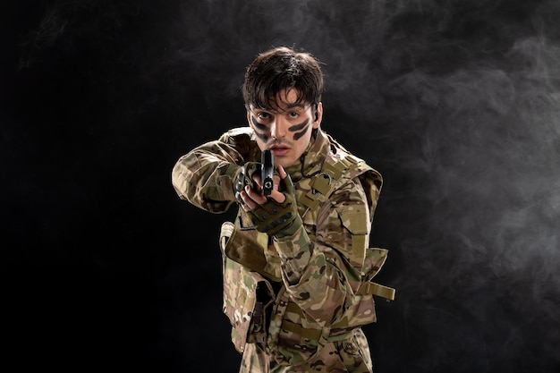 Front view of male soldier in camouflage aiming gun on black wall