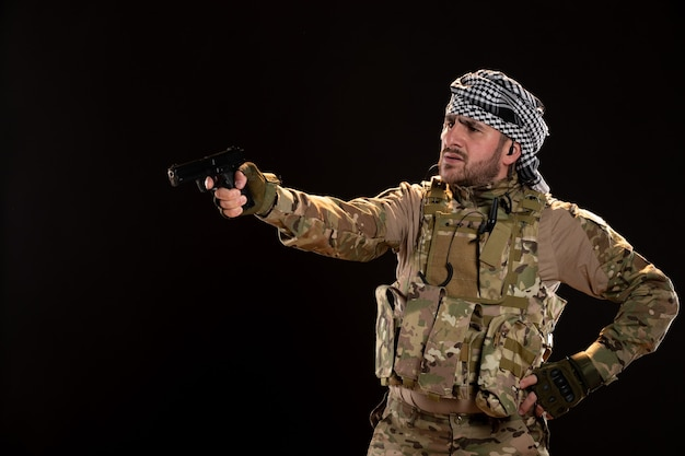Vista frontale del soldato maschio in mimetica che mira pistola sul muro nero