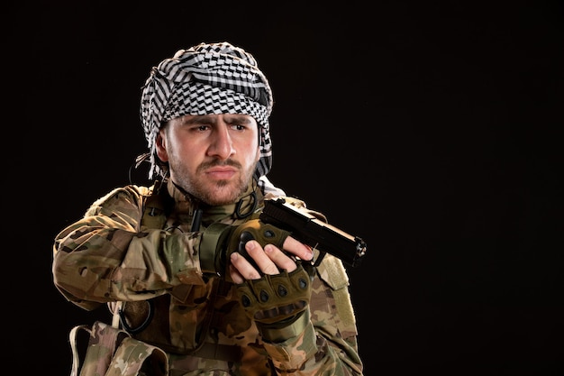 Front view of male soldier in camouflage aiming gun on the black wall