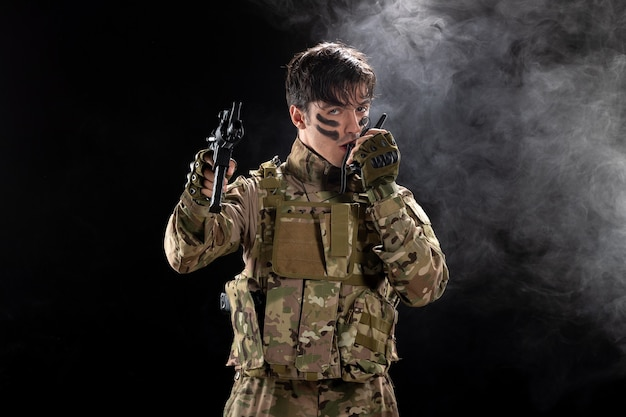 Front view of male soldier in camouflage with rifle black wall
