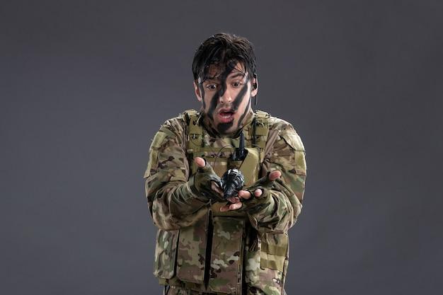 Vista frontale del soldato maschio durante l'operazione militare con una granata su un muro scuro