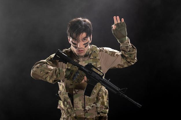Vista frontale del soldato maschio che combatte durante il funzionamento con il fucile sulla parete scura