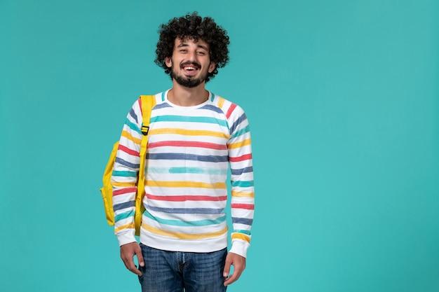 Vista frontale di uno studente maschio in camicia a righe colorate che indossa uno zaino giallo sulla parete blu