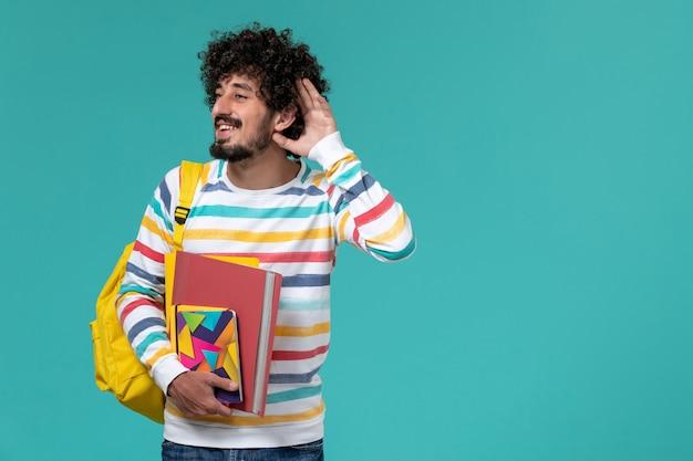 Vista frontale di uno studente maschio in camicia a righe colorate che indossa uno zaino giallo che tiene file e quaderni cercando di ascoltare sulla parete blu