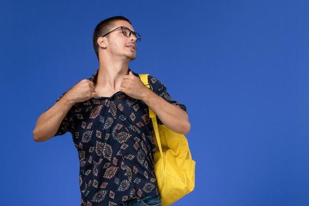Vista frontale di uno studente maschio in camicia di cotone scuro che indossa uno zaino giallo sulla parete blu