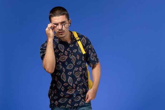 Vista frontale di uno studente maschio in camicia di cotone scuro che indossa uno zaino giallo in posa sulla parete blu