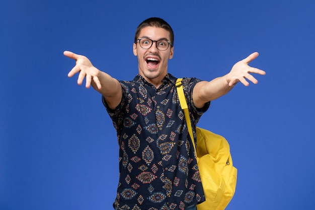 Front view of male student in dark cotton shirt wearing yellow backpack posing and rejoicing on light-blue wall