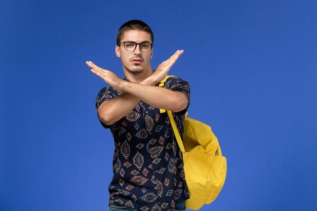Vista frontale di uno studente maschio in camicia di cotone scuro che indossa uno zaino giallo che mostra il segno di divieto sulla parete blu