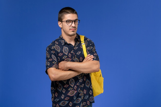 Front view of male student in dark cotton shirt wearing yellow backpack wearing optical sunglasses posing on blue wall