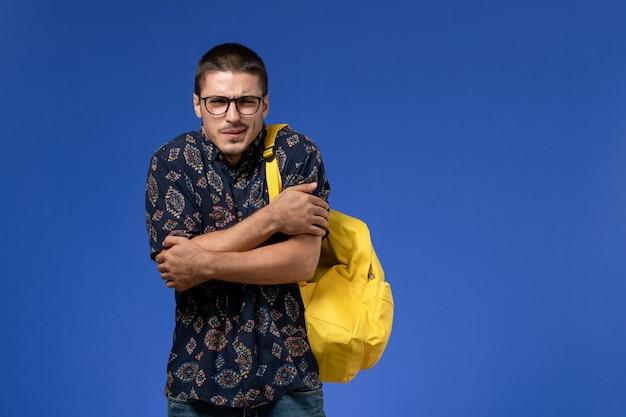 Vista frontale di uno studente maschio in camicia scura che indossa uno zaino giallo sulla parete blu