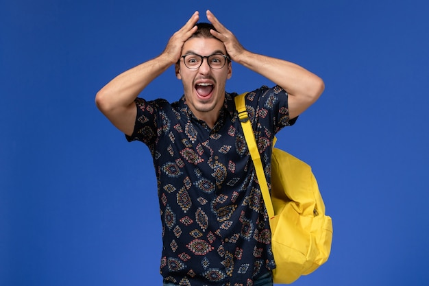 Vista frontale di uno studente maschio in camicia scura che indossa uno zaino giallo sulla parete blu chiaro