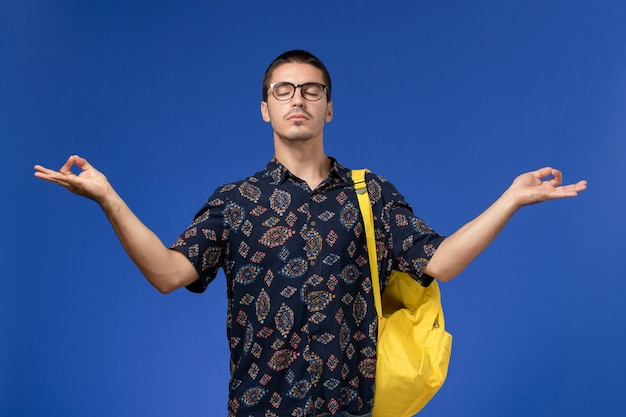 Front view of male student in dark shirt wearing yellow backpack in meditation pose on the blue wall