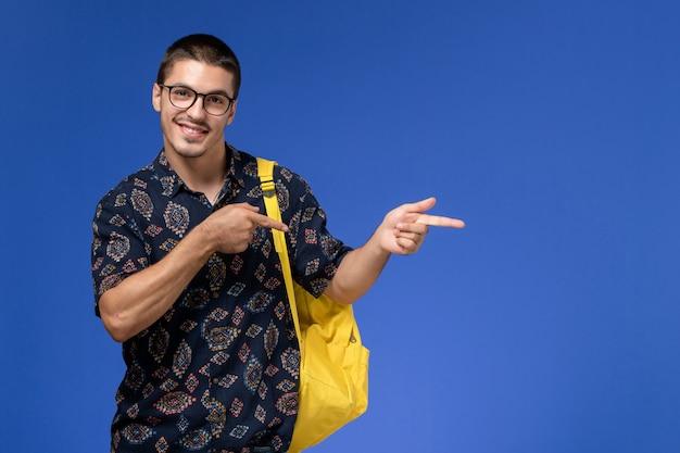 Vista frontale di uno studente maschio in camicia scura che indossa uno zaino giallo e sorridente sulla parete blu