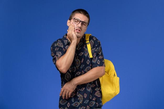 Vista frontale di uno studente maschio in camicia scura che indossa uno zaino giallo che soffre di mal di denti sulla parete azzurra