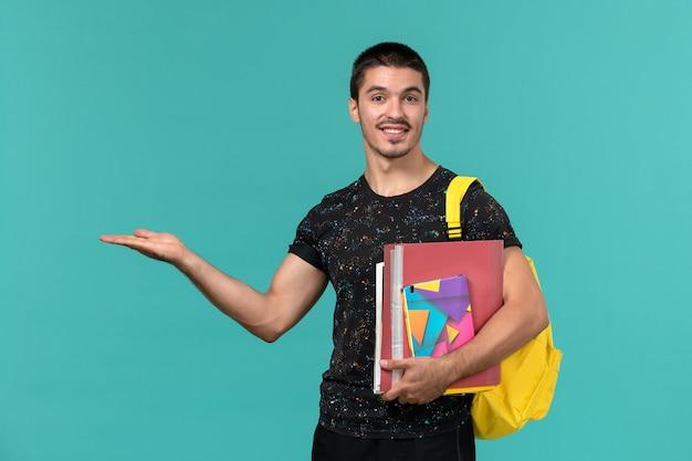 Vista frontale dello studente maschio in maglietta scura che indossa lo zaino giallo che tiene il quaderno e file sulla parete blu