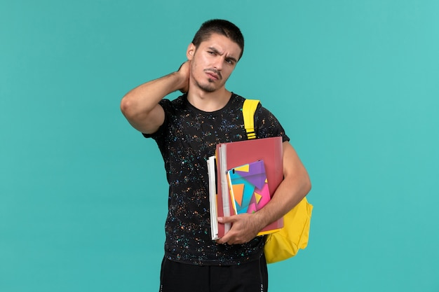 Front view of male student in dark t-shirt wearing yellow backpack holding copybook and files having neckache on blue wall