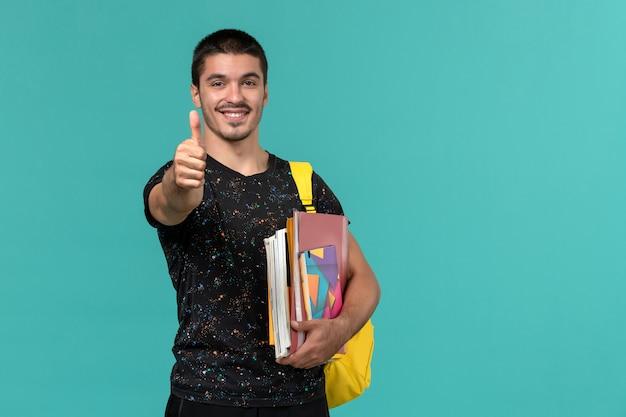 Vista frontale dello studente maschio in maglietta scura che indossa lo zaino giallo che tiene il quaderno e file sorridenti sulla parete blu