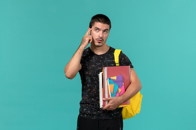 Front view of male student in dark t-shirt wearing yellow backpack holding copybook and files thinking on the blue wall