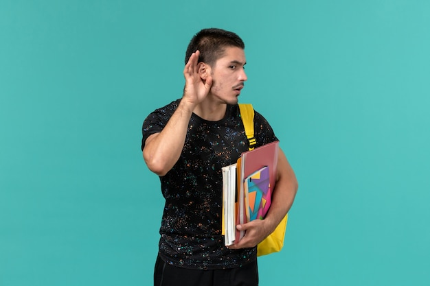 Front view of male student in dark t-shirt wearing yellow backpack holding copybook and files trying to hear on blue wall