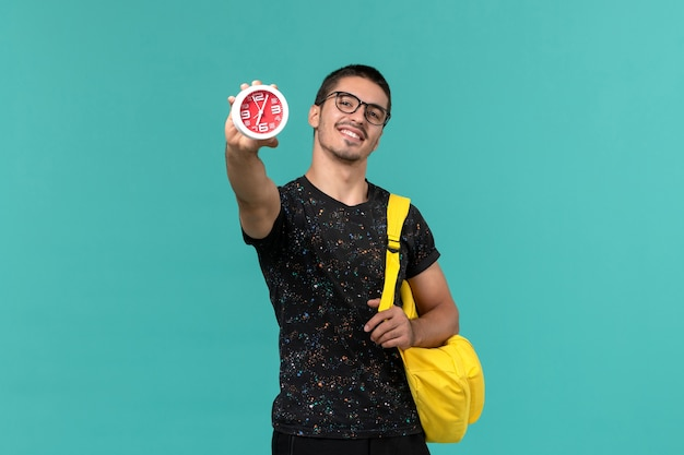 Vista frontale di uno studente maschio in t-shirt scura zaino giallo che tiene gli orologi sulla parete blu