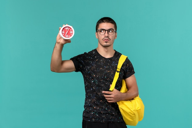 Front view of male student in dark t-shirt yellow backpack holding clocks on blue wall