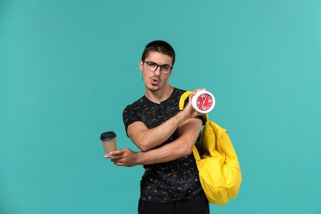 Vista frontale dell'allievo maschio nello zaino giallo della maglietta scura che tiene caffè e orologi sulla parete blu