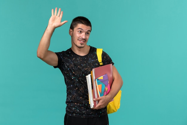 Front view of male student in dark t-shirt yellow backpack holding copybook and files on blue wall